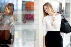 Shopwindow d'esame sorridente della giovane donna nel centro commerciale fotografia stock libera da diritti