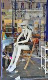 Shopwindow with a dummy and many reflections. A female mannequin is sitting in the showcase. The ancient buildings and passersby are reflected on the glass Stock Image