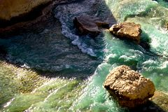 Shore. Water flowing around rocks stock photography