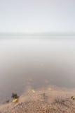 Shore of autumnal foggy lake. Beautiful polish landscape photographed in september at bad weather Stock Image