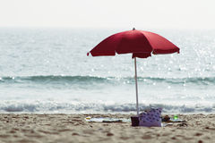 Shore and beach umbrella. Shore line with a red beach umbrella in the sand royalty free stock photography