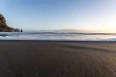 Shore Break Beach. A foamy wave rolls into the shore at Piha Beach, New Zealand Stock Image