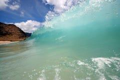 Shore break wave. A wave breaks along a scenic backdrop Royalty Free Stock Photos