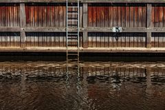 Shore channel with stairs and reflection in water on Dane river in Klaipeda, Lithuania. Shore channel with stairs and reflection in water on Dane river in stock photography