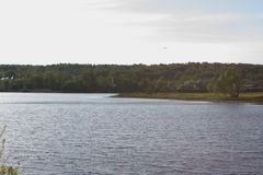 On the shore of a circular lake. The lake and green forest Royalty Free Stock Photo