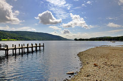 Shore of Coniston Water and jetty. A wooden jetty projecting into Coniston Water in the English Lake District, Cumbria Royalty Free Stock Photos