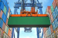 Shore crane loading containers in freight ship.  Stock Images