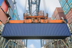 Shore crane loading containers in freight ship.  Stock Photos