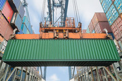 Shore crane loading containers in freight ship Stock Photography