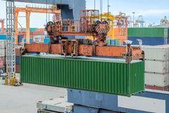 Shore crane loading containers in freight ship (selective focus) Royalty Free Stock Image