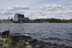Shore with a flower in foreground and a water power plant in bac Stock Photo
