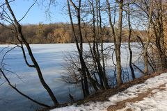 The shore of the forest lake in early spring. Silence and beauty. The snow begins to melt on the road royalty free stock photo