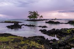 Shore in Hilo, Hawaii at sunrise. Rocky shore, trees, rocks offshire, clear water. Cloudy sky. royalty free stock photography