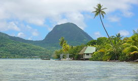 Shore of an islet Huahine island French Polynesia. Shore of an islet with an house and the mount Moua Tapu in background, Huahine island, south Pacific, French royalty free stock image