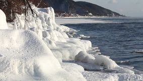 The shore of Lake Baikal is covered with ice and splashes with snowy trees, the water soars against the backdrop of the stock video footage
