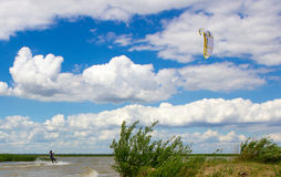 On the shore of the lake in the city of Kokshetau city in Kazakhstan. Landscape in the frame of which was a man rolling around in the surf with a parachute. In Royalty Free Stock Photo