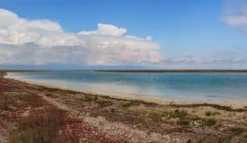 The shore of Lake Karakol in Kazakhstan, Aktau. Beautiful clouds hang very low over the lake. Panorama of steppe. Royalty Free Stock Images