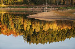 The shore of the lake and trees in autumn colors reflecting on the lake Royalty Free Stock Photos
