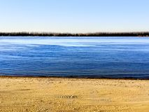 Volga Bank. Volga spaces. The shore of the largest in Europe, the Volga River. Dark waters wash the yellow sandy shore. Blue sky creates contrast stock photo