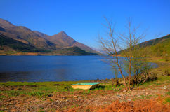 Shore of Loch Leven Lochaber Scotland uk with rowing boat out of the water Stock Photo