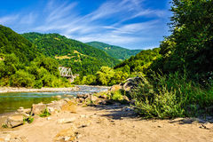 Shore of a river in mountain rural area. Shore of a mountain river with stones and iron bridge among the forest in fural area Royalty Free Stock Photo