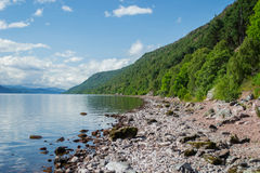 Shore of Scotland's Loch Ness. A view of Scotland's Loch Ness sandy shore. Taken on the shoreline to capture the reflection during a sunny day. Great white Stock Images