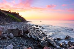 On the shore of the sea covered with stones opens a view on a beautiful landscape of a sunset. stock photography