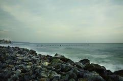 The shore of the sea, the destroyed pier, the gray calm sea. Long exposure. stock photos