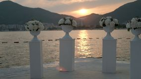 On shore there are columns with flowers on background of summer sunset. Among mountains shore is decorated with floristry for holiday at dusk stock footage