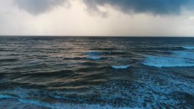 Aerial of sea leaving in the horizon under the cloudy sky in Sri Lanka. The shore is washed by waves of the sea, behind which lies the horizon under the cloudy stock video footage