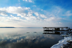 Shore winter sea. The old pier. Ice floes on the water. Sea and ocean in winter and early spring. View of the snowy shore Stock Photo