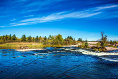 On the shore is a wooden bench. Thin flying cirrus clouds and broad Winnipeg River. Landscape in the Old Pinawa Dam Park. Trend of travel `Around the World`. On Royalty Free Stock Image