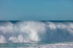 Huge surfing waves crashing in ocean water. Shorebreak wave breaking front view. Image has copyspace at clean light blue sky Stock Photos