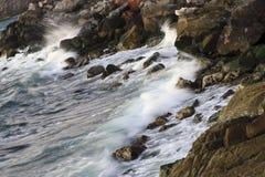 Shoreline. Waves breaking on a stony shoreline forming spray royalty free stock image