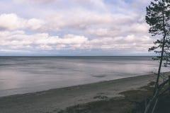 Shoreline of Baltic sea beach with rocks and sand dunes - vintag. Shoreline of Baltic sea beach with rocks and sand dunes under clouds - vintage retro look Stock Photos