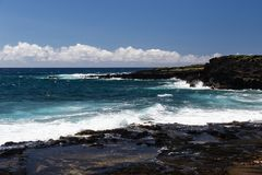 Hawaiian coastline, Big isand. Blue ocean, waves, black lava rock. Blue sky and clouds. Shoreline on Big Island of Hawaii near South Point. Deep blue Pacific royalty free stock photo