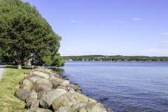 Shoreline at Canandaigua Lake, NY. Sidewalk along the shore of the lake. View across the calm lake stock photos