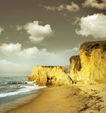 Shoreline cliffs in golden light. Ocean shoreline landscape with sand and cliffs in golden morning light and gray sky above Royalty Free Stock Photo
