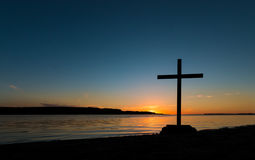 Shoreline Cross Sunset. Black cross at sunset by a river shoreline Stock Photography