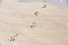 Shoreline with footprints on the sand Stock Photos