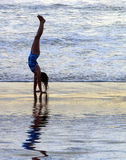 Shoreline Handstand. A young girl joyfully practicing handstands at the water's edge Royalty Free Stock Photos