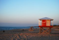 Red lifeguard station waits silently on a deserted beach royalty free stock photography