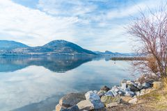 Rocky shoreline of breakwater with calm lake reflecting sky and mountains in early spring. Shoreline of Marina Way Park and the breakwater near the Penticton Royalty Free Stock Photos