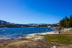 Shoreline At Mountain Lake In Springtime. With Choppy Waves & Snow On Mountains Royalty Free Stock Image