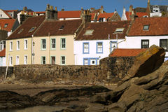 Shoreline properties. A row of historic seafront properties with traditional orange pantiled roofs and painted walls in the old fishing village of Pittenweem in Royalty Free Stock Image