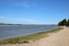 Shoreline River Kent estuary, Arnside viaduct, UK. View towards Arnside railway viaduct looking along the shoreline footpath as the recent high tide ebbs on a royalty free stock photo