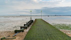 Shoreline of the River Thames at low tide in Southend-on-Sea. Shoreline of the River Thames at low tide with a boat and Southend Pier in the background, Southend Stock Photo