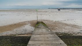 Shoreline of the River Thames at low tide in Southend-on-Sea. Shoreline of the River Thames at low tide with a boat and Southend Pier in the background, Southend Stock Photos
