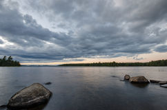 Shoreline Rocks. Rocks break up the glassy water during a wilderness sunset Stock Photography