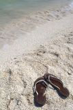 Shoreline with sandals. Beach with sandals on the shore Stock Image
